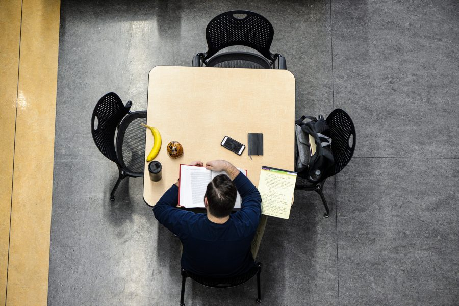 Seen in an overhead view, a man settles in for a morning of snack-fueled studying in the student lounge and atrium of the Law School Building at the University of Wisconsin-Madison