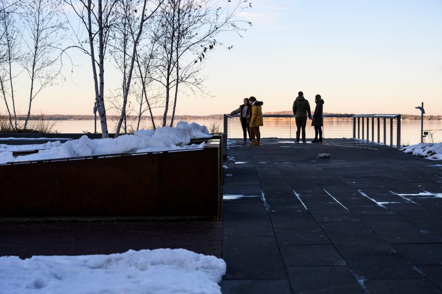 Pedestrians take in a sunset view of partially frozen Lake Mendota