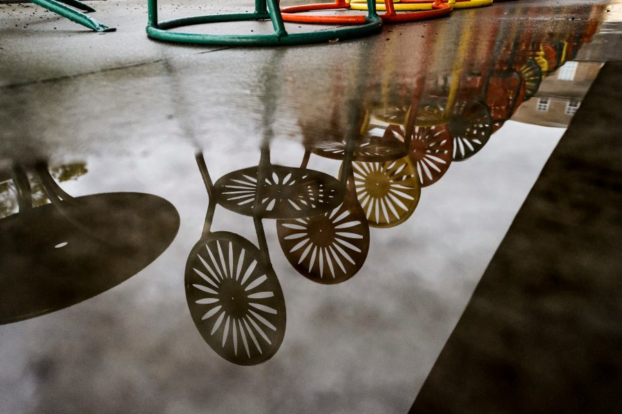 Puddled-rain water reflects an image of the Memorial Union Terrace chairs and their iconic sunburst design following a passing summer thunderstorm at University of Wisconsin-Madison