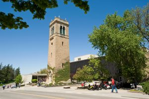 Trees and pedestrians frame a view of the Carillon Tower in front of the Sewell Social Sciences building