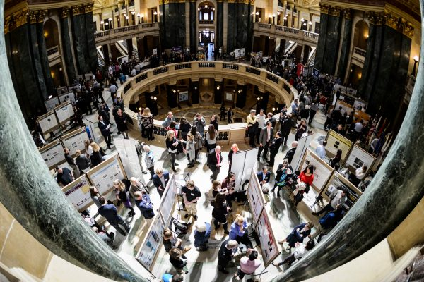 UW-Madison students, at bottom, present their research project displays as people fill the Wisconsin State Capitol during Research in the Rotunda on April 11, 2018. The outreach event provides students and faculty advisors from across the UW System with the opportunity to share their research findings with Wisconsin legislators, state leaders, UW alumni and members of the public.