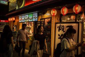 Photo of people walking along a city sidewalk in Japan