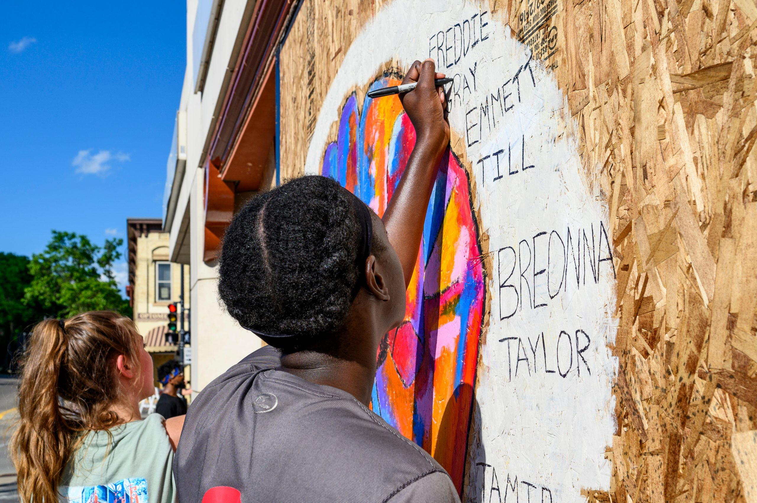 UW-Madison students (near to far) Courtney Gorum, Molly Pistono and Daniel Ledin work together to paint a mural commemorating the names of Black victims of police violence and racial injustice throughout the country on a boarded up window of the Community Pharmacy building on State Street in Madison, Wisconsin on June 5, 2020. The mural is one of many that have been painted on businesses and shops along the street following several nights of protests in response to the Minneapolis police killing of George Floyd, a black man, on May 25, 2020. (Photo by Bryce Richter / UW-Madiso